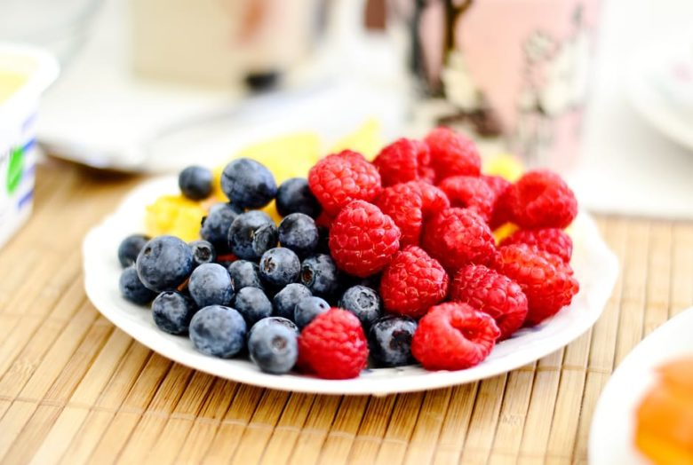 A plate of blueberries and raspberries