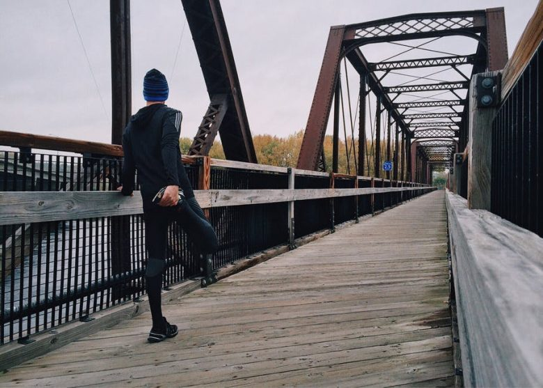 a man on a bridge getting ready to run