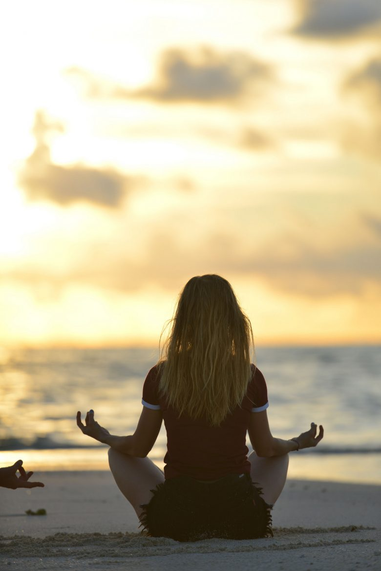 A girl meditating at the beach