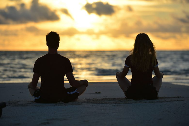 Agness and Cez at the beach meditating